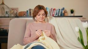 La mujer adulta hermosa está haciendo punto una manta en el sitio acogedor en casa que se sienta en el sofá metrajes