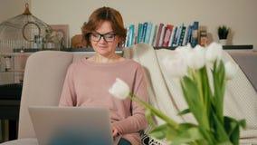 La mujer adulta hermosa está utilizando el ordenador portátil que se sienta en el sofá en un cuarto acogedor en casa almacen de video