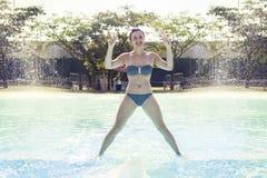 La mujer adulta joven en traje de baño hace la gimnasia Imagen de archivo libre de regalías