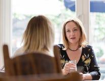 La mujer adulta joven escucha el opositor en el meetin informal del negocio imagen de archivo
