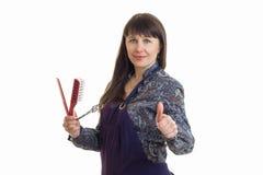 La mujer adulta linda del estilista con las herramientas en manos muestra los pulgares para arriba Foto de archivo
