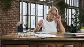 La mujer adulta ocupada con los papeles y las cuentas está haciendo informe con la calculadora en Ministerio del Interior Negocio almacen de metraje de vídeo
