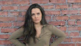 La mujer adulta representa enojado, jura in camera bastidor Fondo de la pared de ladrillo metrajes