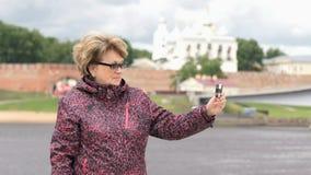 La mujer adulta toma las fotos usando el teléfono elegante de plata metrajes