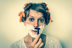 La mujer afeita su cara con la espuma y la maquinilla de afeitar - estilo retro imagen de archivo libre de regalías