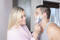 La mujer a afeitar es novio en cuarto de baño Fotos de archivo