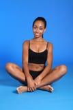 La mujer africana atlética de la aptitud sienta legged cruzado Imagenes de archivo