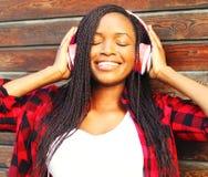 La mujer africana bastante joven con los auriculares está gozando escucha Imagen de archivo