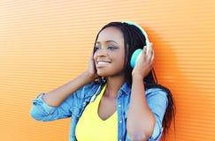 La mujer africana bastante sonriente con el goce de los auriculares escucha la música sobre naranja Imagenes de archivo