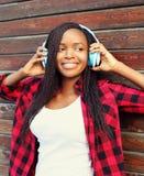 La mujer africana bastante sonriente con el goce de los auriculares escucha música en ciudad Imagen de archivo libre de regalías
