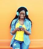 La mujer africana bastante sonriente con los auriculares escucha la música sobre naranja Fotos de archivo