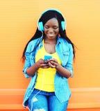 La mujer africana bastante sonriente de la moda con los auriculares escucha la música sobre naranja Foto de archivo