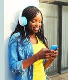 La mujer africana bastante sonriente de la moda con los auriculares escucha la música usando smartphone en ciudad Imagen de archivo libre de regalías