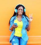 La mujer africana bastante sonriente de la moda en los auriculares escucha la música sobre fondo anaranjado Imagen de archivo libre de regalías