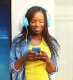 La mujer africana bastante sonriente de la moda en los auriculares escucha la música usando smartphone en ciudad Foto de archivo