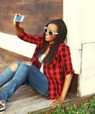 La mujer africana bastante sonriente de la moda hace el autorretrato en smartphone Foto de archivo