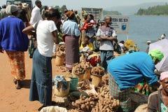 La mujer africana compra patatas dulces. Foto de archivo libre de regalías