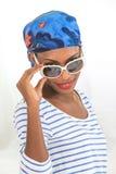 La mujer africana con la moda que lleva del pañuelo observa los vidrios Foto de archivo