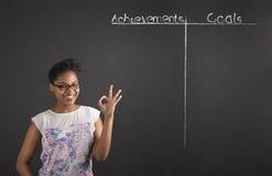 La mujer africana con la señal de mano perfecta con los logros y las metas enumera en fondo de la pizarra Foto de archivo libre de regalías