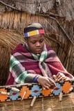 La mujer africana del Zulú teje la alfombra de la paja Imagen de archivo libre de regalías
