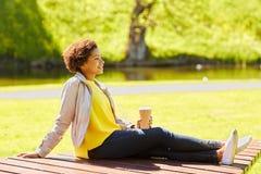 La mujer africana feliz bebe el café en el parque del verano Foto de archivo