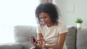 La mujer africana feliz que birla en el teléfono que fecha el app siente emocionada almacen de metraje de vídeo