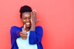 La mujer africana joven alegre que muestra los pulgares sube la muestra Imagen de archivo