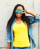 La mujer africana joven bastante sonriente del retrato de la moda en las gafas de sol se está divirtiendo Imágenes de archivo libres de regalías