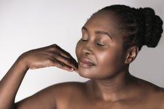 La mujer africana joven con ella los ojos cerró el tacto de su barbilla imagen de archivo