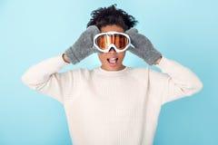 La mujer africana joven en concepto azul del deporte de invierno del estudio de la pared puso gafas imagen de archivo