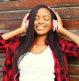 La mujer africana joven sonriente feliz del retrato de la moda con el goce de los auriculares escucha la música Imagen de archivo