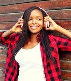 La mujer africana joven sonriente feliz del retrato de la moda en el goce de los auriculares escucha la música Imagenes de archivo