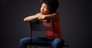 La mujer africana que se sienta ocasional con los brazos encima apoya de silla Imagen de archivo libre de regalías