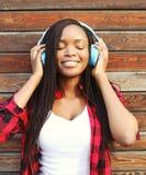 La mujer africana sonriente con el goce de los auriculares escucha la música en ciudad Fotografía de archivo
