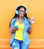 La mujer africana sonriente feliz con el goce de los auriculares escucha la música sobre naranja Foto de archivo