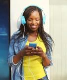 La mujer africana sonriente hermosa con los auriculares escucha la música Fotografía de archivo libre de regalías