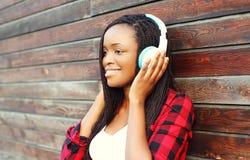 La mujer africana sonriente hermosa con los auriculares escucha la música Imagen de archivo libre de regalías