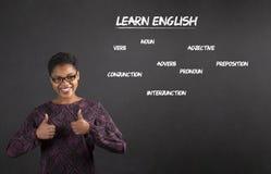 La mujer afroamericana con los pulgares encima de la señal de mano aprende inglés en fondo de la pizarra imagen de archivo