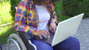 La mujer afroamericana con un peinado afro discapacitado en una silla de ruedas utiliza un sunflare del ordenador portátil almacen de metraje de vídeo
