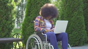 La mujer afroamericana con un peinado afro discapacitado en una silla de ruedas utiliza un sunflare del ordenador portátil en par almacen de metraje de vídeo