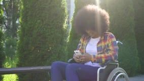 La mujer afroamericana con un peinado afro discapacitado en una silla de ruedas utiliza un sunflare del smartphone metrajes