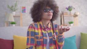 La mujer afroamericana con una persona con deficiencias visuales afro del peinado consume al ayudante de la voz en su cierre del  almacen de metraje de vídeo