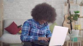La mujer afroamericana discapacitada del retrato con un peinado afro en una silla de ruedas utiliza un ordenador portátil almacen de video