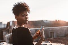 La mujer afroamericana está fotografiando paisaje urbano Foto de archivo