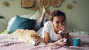La mujer afroamericana está viendo la TV el sostener de los botones acuciantes teledirigidos y el reír mientras que está mintiend metrajes