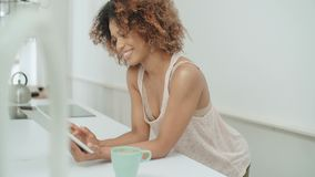La mujer afroamericana feliz sonriente que usa la PC hace tabletas en casa almacen de video