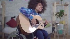 La mujer afroamericana inhabilitada con un peinado afro en una silla de ruedas juega cierre de la guitarra acústica para arriba metrajes