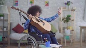 La mujer afroamericana inhabilitada con un peinado afro en una silla de ruedas toma un selfie con una guitarra acústica almacen de video