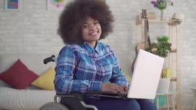 La mujer afroamericana inhabilitada con un peinado afro en una silla de ruedas utiliza un ordenador portátil que mira la cámara almacen de metraje de vídeo