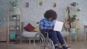 La mujer afroamericana inhabilitada con un peinado afro en una silla de ruedas utiliza un ordenador portátil almacen de metraje de vídeo
